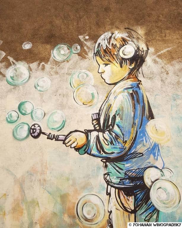 street art par alice pasquini à vitry sur seine gamin qui fait des bulles de savon