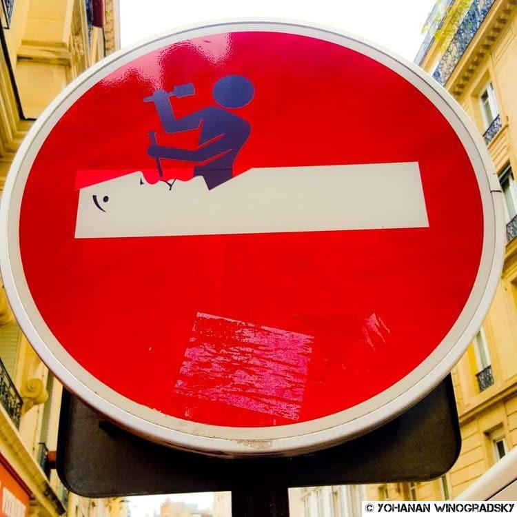 streetart par clet abraham à paris sculpteur sur panneau de sens interdit