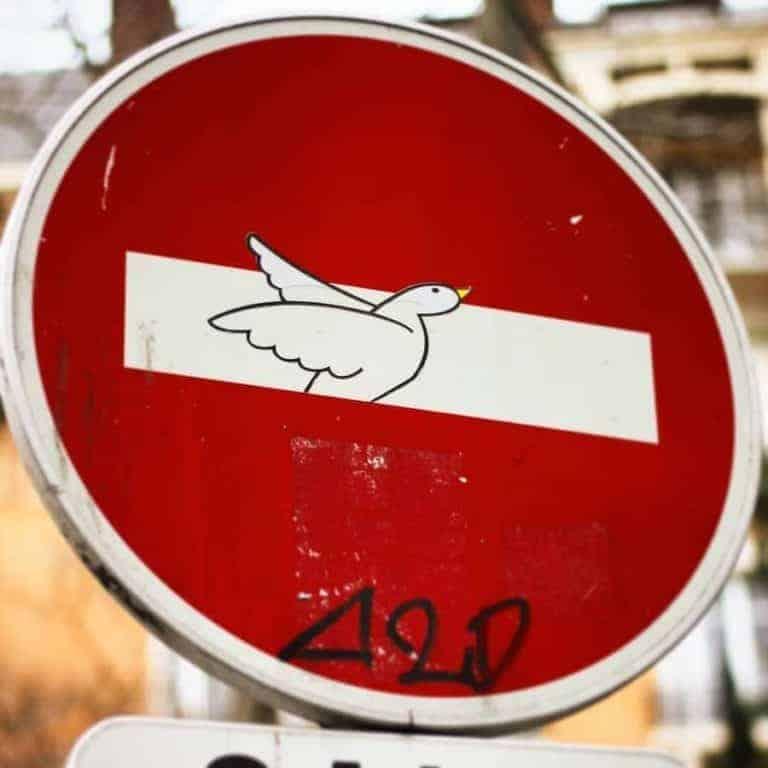 street art paris par clet abraham, panneau de sens interdit avec envol d'un oiseau