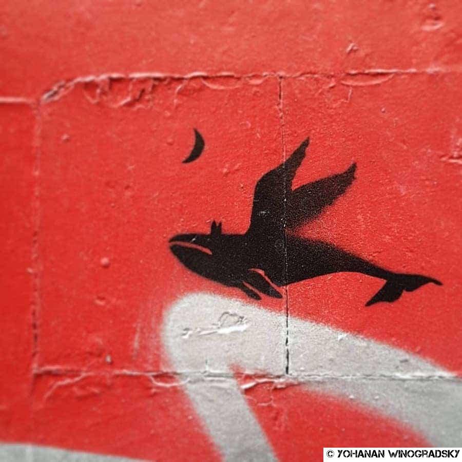 street art paris anonyme pochoir d'une baleine ailée s'envolant vers la lune